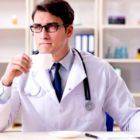 Medico che beve il caffè